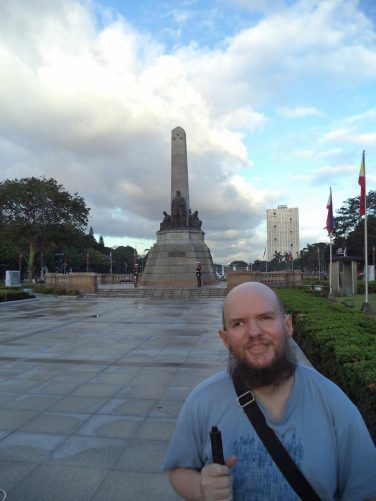 Tony with the Rizal Monument behind. The monument, commemorating national hero José Rizal, was constructed between 1908 and 1913. The monument consists of a standing bronze statue of Rizal, with an obelisk behind, set on a stone base within which his remains are interred. It is located in Rizal Park.