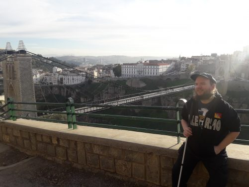Tony sitting with the old city and the Sidi M'Cid Bridge in the background.