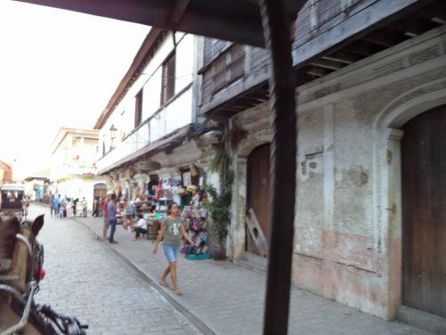 Travelling along Calle Crisologo, the main old colonial street of Vigan. In view are old colonial-era houses built of stone and wood with souvenir shops at street level. The shot was taken from a kalesa, an old-fashioned horse-drawn carriage that locals used to traverse the city in Spanish times.