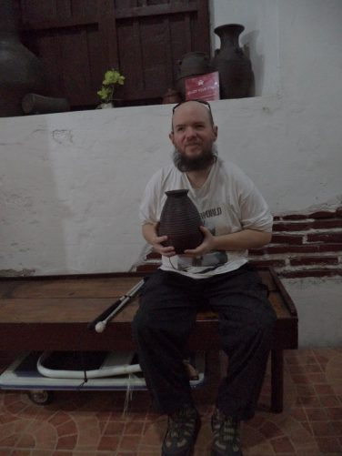 Tony sitting on a bench in Escolta's Homey Lodge, holding a small, but heavy clay pot. The item may have belonged to the original owners of the building. Pottery is still made in Vigan.