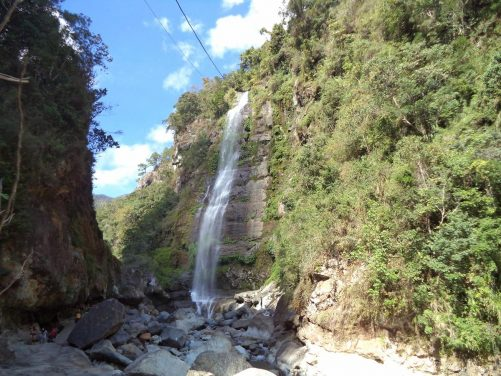 The end of the trail at Bomod-Ok Falls. This is the biggest waterfall in the Sagada area. A single column of water drops from a smooth cliff, approximately (61 metres or 200 feet) into a rocky pool of cold water where people can swim.