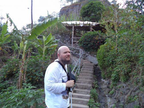 Tony heading back up the 4,000 steps. Vegetation, including palms, along the path.