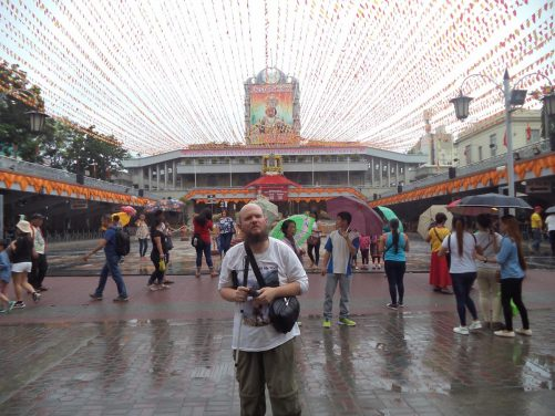 Tony in a large courtyard decorated with orange and red bunting outside the Basilica of Santo Niño. The modern building in the background is the Pilgrim Center, which was built in 1990 to help accommodate the large number of worshippers who visit the site. Outdoor services are held here.