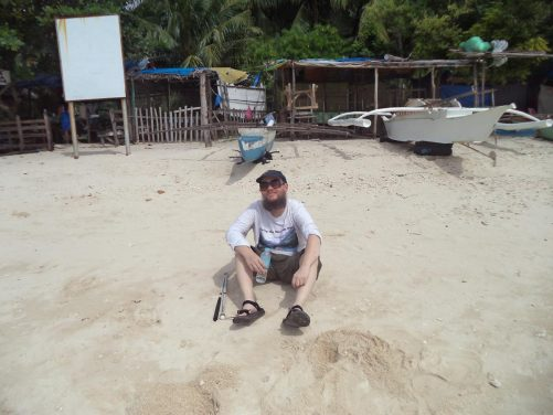 Tony sitting on White Beach. A couple of small boats on the sand behind.