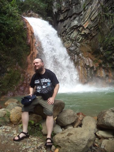 Tony sat on a rock right in front of the falls, reached after crossing a knee-deep river with help.