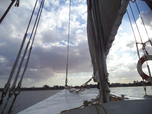 View across the Nile from the bow as the boat sets off. The base of the mast immediately in front.
