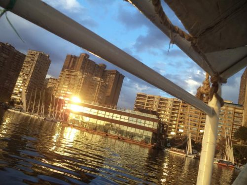 The setting sun reflecting on the windows of buildings as the boat passes along the river.