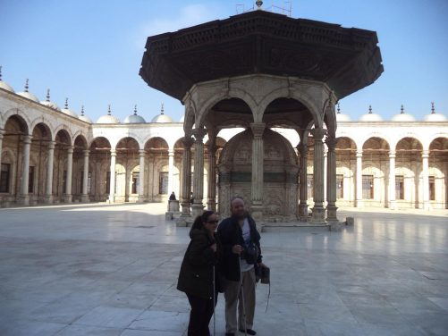 Tony and Tatiana in the courtyard of Muhammad Ali Mosque. Behind is a large shadirvan, a fountain often found near the entrance of mosques, used for ritual washing by Muslims before prayer. The fountain is shaded by an octagonal roof.