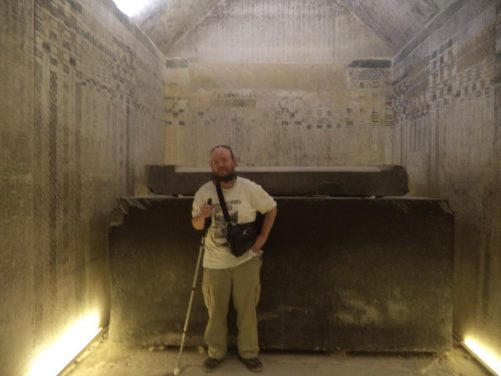Tony inside the burial chamber of Unas Pyramid. The burial chamber's basalt sarcophagus is in view as well as carved and painted inscriptions and decoration on the walls and ceiling.
