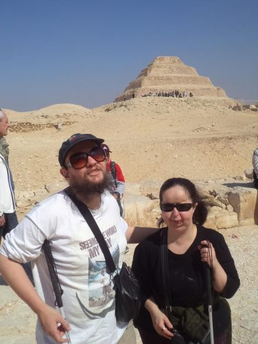 Tony and Tatiana with a view towards Djoser Pyramid (also known as Step Pyramid). The pyramid has six stepped levels and was originally clad in polished white limestone. It was built during the 3rd dynasty of the Old Kingdom (circa 2686 – 2613 BC) for the burial of Pharaoh Djoser. It was originally 62.5 metres in height and 121 metres by 109 metres along its base.