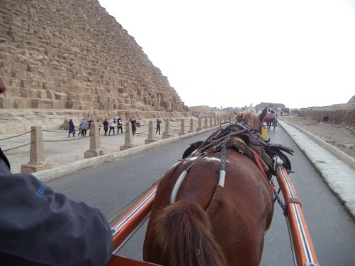 Onboard a horse-drawn carriage passing alongside the Great Pyramid of Giza (also known as the Pyramid of Khufu). Constructed circa 2580–2560 BC during the 4th dynasty. It is the oldest of the Seven Wonders of the Ancient World and the only one still in existence. It was originally 146.7 metres in height (now 139 metres) and is 230 metres along its base.
