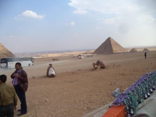 Another view of the Pyramid of Menkaure and the surrounding desert landscape. Camels sitting in the foreground.
