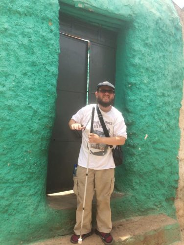 Tony outside the doorway to a house in the Old City. The walls are painted bright green.