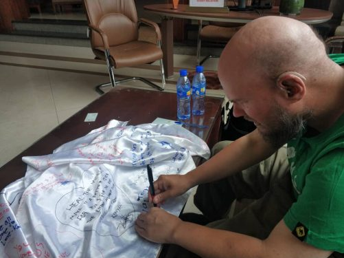 Tony signing a silk sheet belonging to Happy. All of his guests sign it with a message of thanks or something meaningful.