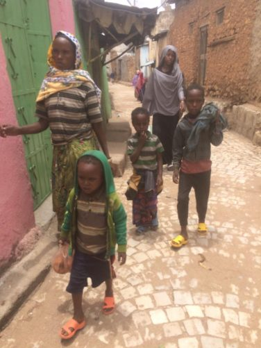 Two local women and three children walking along a street.