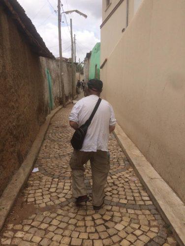 Tony walking along a narrow street.