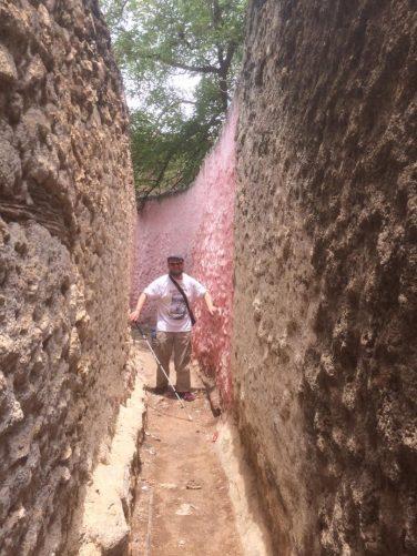Tony walking along narrow 'Peacemaker Alley' touching the walls at both sides.