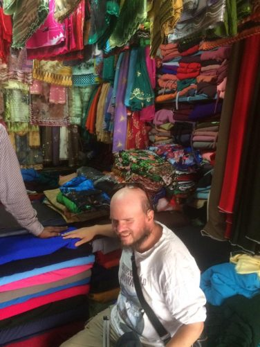Tony met  a man near to the museum who saw him before on the BBC and wanted to take him to his shop full of brightly coloured silks. Tony touching a silk sheet.
