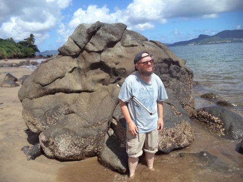 Tony in front of a large interestingly shaped rock at the edge of the sea. It is vaguely in the shape of a lion's head.