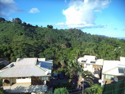 Looking from the balcony at the Airbnb house where Tony stayed. Located in a village roughly four kilometres from Mamoudzou, Mayotte's capital town in the north of Grande-Terre. Other surrounding houses can be seen with a wooded hill beyond.