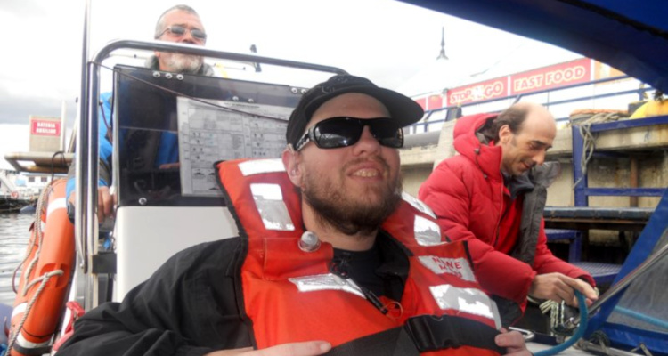 Tony sitting in a large Zodiac inflatable boat. He's about to travel across the Beagle Channel to Navarino Island in Chile, February 2011.